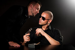 Mafia man telling a boss with gun some news. Mafia men whispering on the ear a boss sitting in the dark room with gun and glass of alcohol some news royalty free stock photo