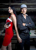 Mafia man and woman in warehouse. A couple dressed like Mafia.  Man with cigar in his mouth and lady with large revolver in a bright red dress Royalty Free Stock Photos
