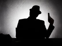 Mafia shadow. Silhoutte of retro style gangster holding his gun on grunge background Royalty Free Stock Image