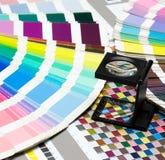 Mafnifying exponeringsglas överst av den Pantone färghandboken Royaltyfri Fotografi