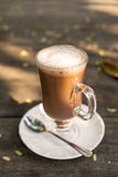 Mag of hot cocoa and foam. On wooden table Royalty Free Stock Photo