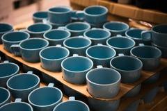Magasin coloré de tasse Tasses bleues de couleur d'Aqua se tenant dans la boutique photos stock