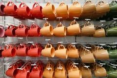 Magasin coloré de tasse tasses de différentes couleurs se tenant dans la boutique images stock
