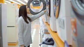 Magasin d'appareils électroménagers Une jeune femme choisit une machine à laver banque de vidéos