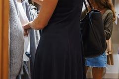 Magasin moderne de mode Les acheteurs choisissent les vêtements images stock