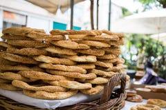 Magasin mycket av grekiska traditionella runda sesambrödcirklar, visat i en gatamarknad med bokehbakgrund Fotografering för Bildbyråer