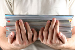 Magazine. Stack of magazines with male hands Royalty Free Stock Photo
