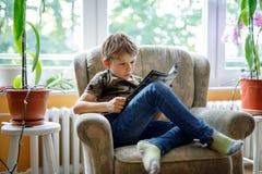 Magazine blonde mignonne de lecture de garçon de petit enfant dans la chambre domestique Image stock