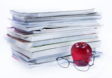 Magazine and book stack with glasses and apple Stock Image