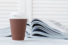 Magazine and coffee to go composition close up shot Stock Photo