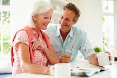 Magazine de lecture de couples âgée par milieu au-dessus de petit déjeuner Photos stock