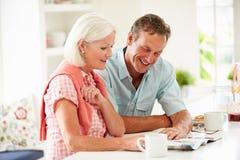 Magazine de lecture de couples âgée par milieu au-dessus de petit déjeuner Images libres de droits