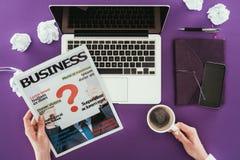 Magazine de lecture de femme d'affaires sur le lieu de travail sur la surface pourpre Photographie stock