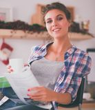 Magazine de lecture de femme dans la cuisine à la maison Photos libres de droits