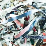 Magazine paper shredded long strips shape. Cut from shredder machine, 1:1 ratio close up picture Royalty Free Stock Photo