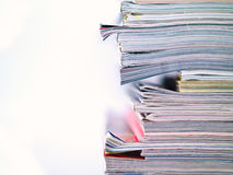 Magazine Stacked Half Frame. An uneven stack of magazines filling the frame from top to bottom with copyspace on left Stock Photos