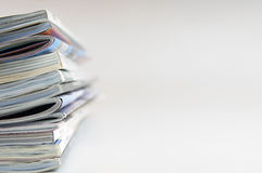 Magazines. Forefront of some magazines piled out of focus white background stock images