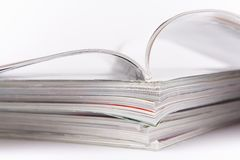 Magazines. Stack of glossy periodical magazines, one open Royalty Free Stock Photo