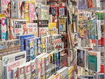 Magazines on display shelf in store. BANGKOK, THAILAND - November 1, 2018 : Lifestyle magazines, travel guide book and souvenir on display shelf for sale in a royalty free stock photos