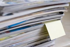 Magazines with post it note. A pile of magazines with a sticky reminder note poking out Stock Photography