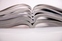 Magazines stack. Open magazines on white table Royalty Free Stock Photo