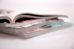 Magazines stack. Open magazines on white table Royalty Free Stock Images