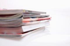 Magazines stack. Open magazines on white table Stock Image