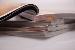 Magazines stack. Open magazines on white table Royalty Free Stock Photography