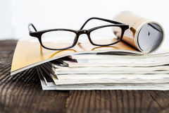 Magazines on table with eyeglasses Stock Images