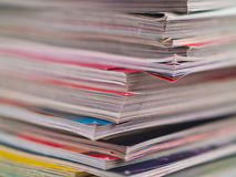 Magazines Unevenly Stacked Edge Focus. An uneven stack of magazines filling the frame from top to bottom focus on corner edge Stock Photography