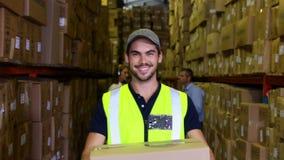 Magazynowy pracownik ono uśmiecha się przy kamerą niesie pudełko zbiory