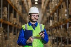 Magazynowy pracownik używa telefon komórkowego obraz stock
