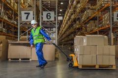 Magazynowy pracownik wlec furę z pudełkami Zdjęcie Stock