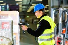 Magazziniere con lo scanner al magazzino di procedimento fotografie stock