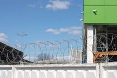 Magazzino dietro il recinto con filo spinato Fotografie Stock