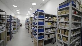 Magazzino industriale Scaffali del metallo bianco con i vassoi blu e le scatole di cartone di plastica installati in loro stock footage