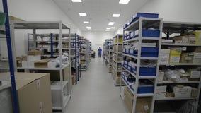 Magazzino industriale Scaffali del metallo bianco con i vassoi blu e le scatole di cartone di plastica installati in loro archivi video