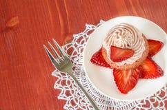 Magdalena de la fresa con la crema de la mantequilla adornada con las rebanadas de fresas frescas Foto de archivo libre de regalías
