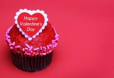 Magdalena del chocolate con el corazón de las tarjetas del día de San Valentín en el top, sobre rojo Imagenes de archivo