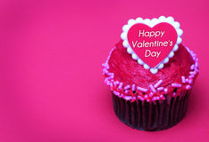 Magdalena del chocolate con el corazón de las tarjetas del día de San Valentín en el top, sobre rosa Fotografía de archivo libre de regalías