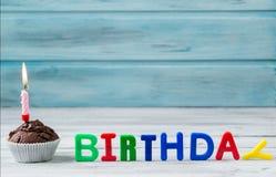 Magdalena del chocolate con la vela y el cumpleaños escritos de letras del imán en fondo de madera Foto de archivo libre de regalías
