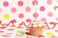 Magdalena del cumpleaños con crema de la mantequilla y vela en fondo colorido Imágenes de archivo libres de regalías