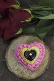Magdalena rosada del corazón con el relleno de Ganache, y rosas rojas Fotos de archivo libres de regalías