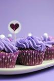 Magdalenas adornadas púrpuras de color de malva - vertical del primer con el espacio de la copia. Imagen de archivo