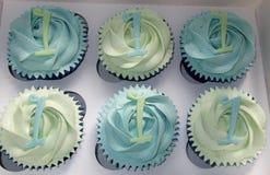 Magdalenas azules y verdes con la decoración del número 1 imagenes de archivo