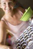 Magdalenas caucásicas sonrientes del chocolate de hornada de la muchacha Fotografía de archivo