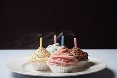 Magdalenas coloridas con las velas del cumpleaños en la placa Foto de archivo
