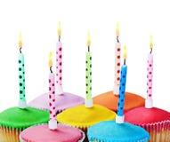 Magdalenas coloridas del feliz cumpleaños con las velas Imagen de archivo libre de regalías