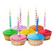Magdalenas coloridas del feliz cumpleaños con las velas Fotografía de archivo libre de regalías