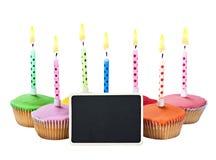 Magdalenas coloridas del feliz cumpleaños con las velas Imágenes de archivo libres de regalías